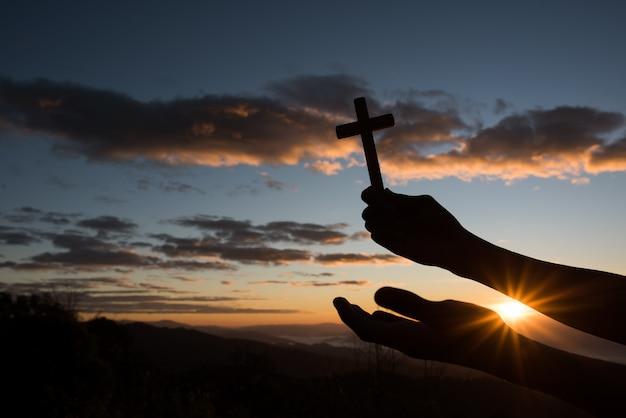 Silhueta de mão segure a cruz de deus Foto gratuita