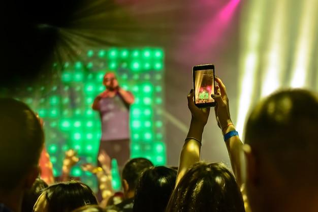 Silhueta de mãos com um smartphone no fundo dos artistas cantores à luz das luzes vermelhas Foto Premium