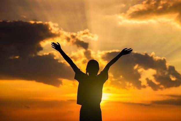 Silhueta de mulher feliz abre os braços no campo de trigo ao pôr do sol Foto Premium