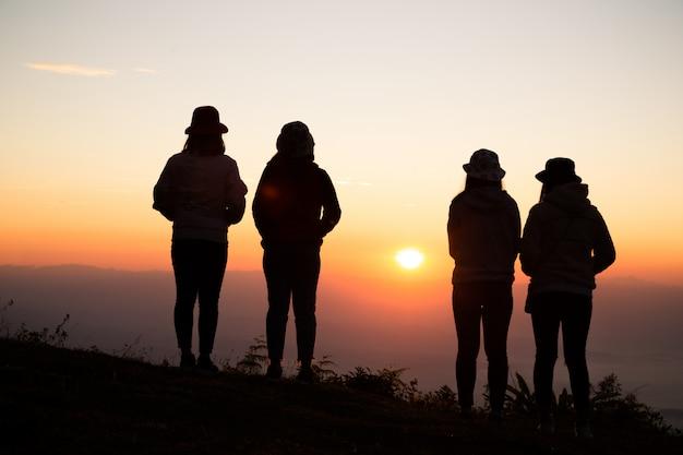 Silhueta de mulher jovem está de pé no topo da montanha relaxante Foto gratuita