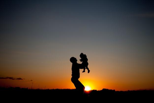 Silhueta de pai e filho no pôr do sol lindo de verão - família Foto Premium