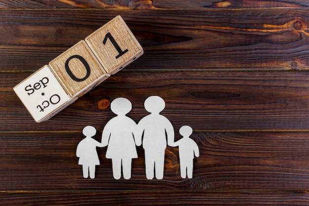 Silhueta de papel da família com o 1º de setembro em um calendário decorativo em de madeira. Foto Premium