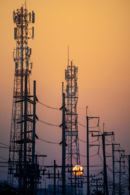 Silhueta de poste elétrico de alta tensão no céu pôr do sol Foto Premium