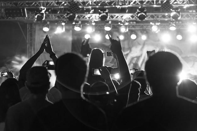Silhueta de preto e branco de pessoas na multidão em um festival de música. concerto com retroiluminado dançando pessoas Foto Premium