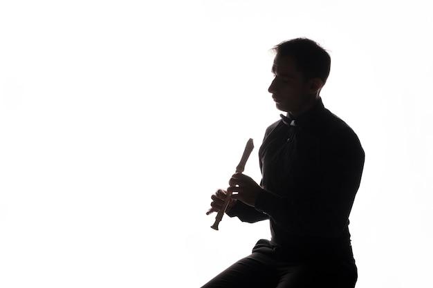 Silhueta de um artista tocando flauta Foto gratuita