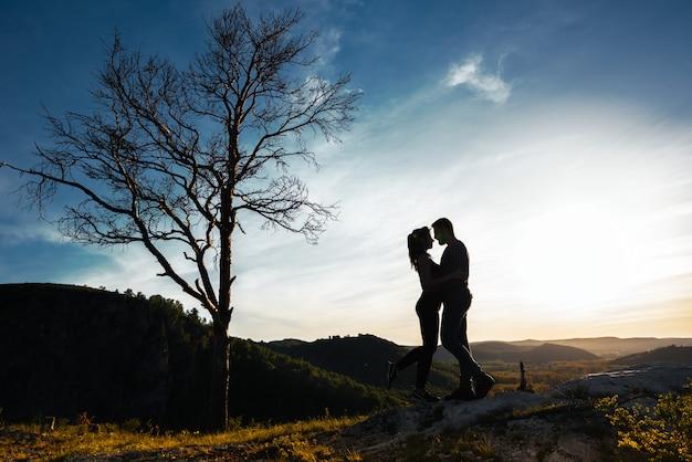 Silhueta de um casal apaixonado. cara e menina abraçando ao pôr do sol. casal viaja. amantes da natureza. homem e mulher assistindo o pôr do sol. amantes ao pôr do sol. viajar nas montanhas. viagem de lua de mel Foto Premium