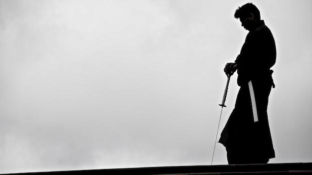Silhueta de um homem japonês no quimono praticando com uma espada de katana japonesa tradicional Foto gratuita