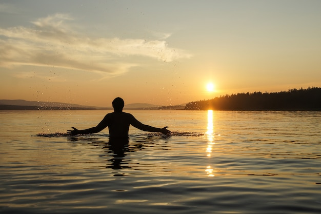 Silhueta de um homem no fundo por do sol. o cara na cintura mergulhou no mar. Foto Premium