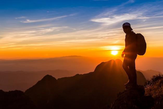Silhueta de um homem no topo de uma montanha. silhueta de pessoa ...