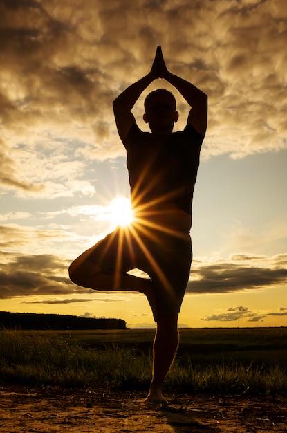 Silhueta de um homem praticando ioga Foto Premium