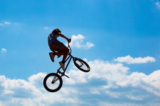 Silhueta de um homem pulando de bicicleta contra um céu azul com nuvens brancas. cara executa truques em uma bicicleta Foto Premium