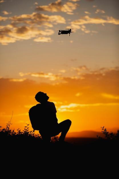 Silhueta de um jovem com uma mochila operando um drone em a rural setting on sunset Foto Premium