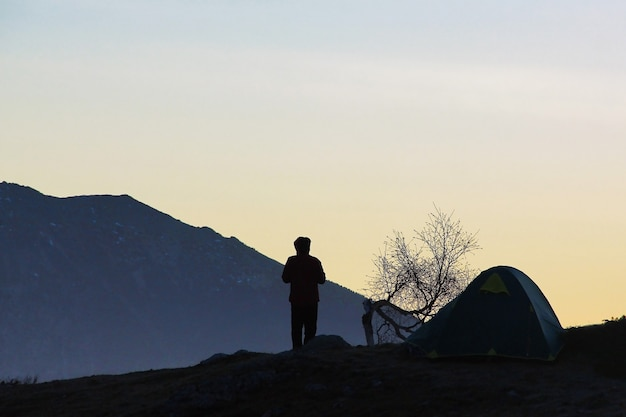 Silhueta de um jovem, uma tenda e uma árvore contra as montanhas Foto Premium