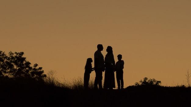 Silhueta de uma família feliz de quatro, mãe, pai, filha, filho ao pôr do sol Foto Premium
