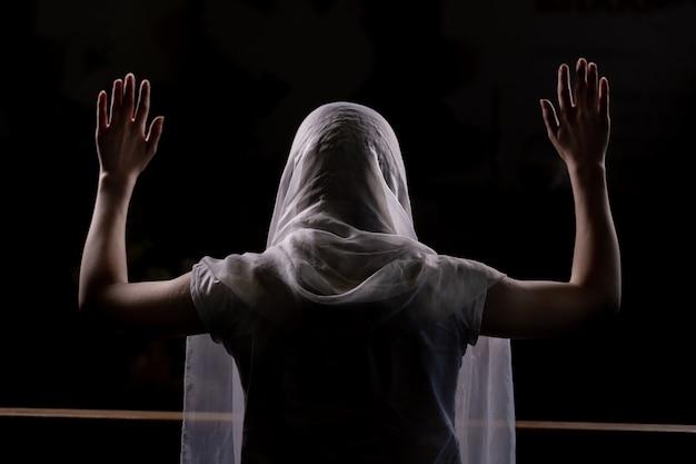 Silhueta de uma jovem garota que se senta na igreja e orando com as mãos levantadas. vista do close-up por trás. luz de fundo Foto Premium