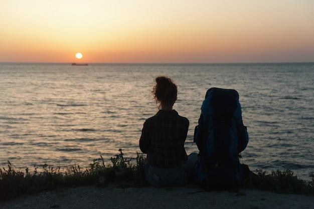Silhueta de uma menina com uma mochila no fundo por do sol Foto Premium