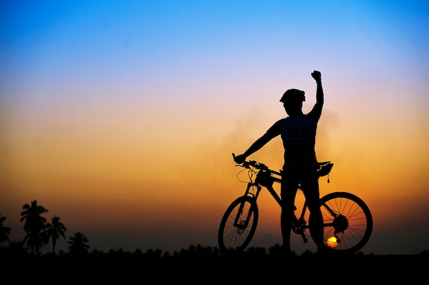 Silhueta do ciclista com a bicicleta de montanha no tempo bonito do por do sol. Foto Premium