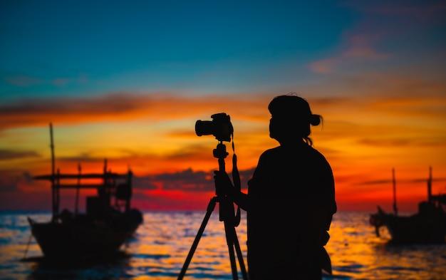 Silhueta do fotógrafo com a hora por do sol. Foto Premium