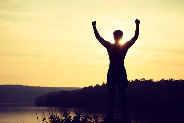 Silhueta do homem do esporte do vencedor no topo da montanha. esporte e conceito de vida ativa Foto Premium