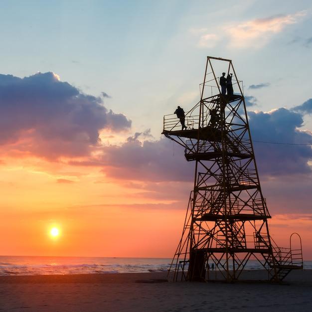 Silhueta dos povos em uma torre do salvamento em uma praia arenosa no por do sol. Foto Premium