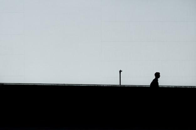 Silhueta horizontal de um homem solitário sob o céu claro Foto gratuita