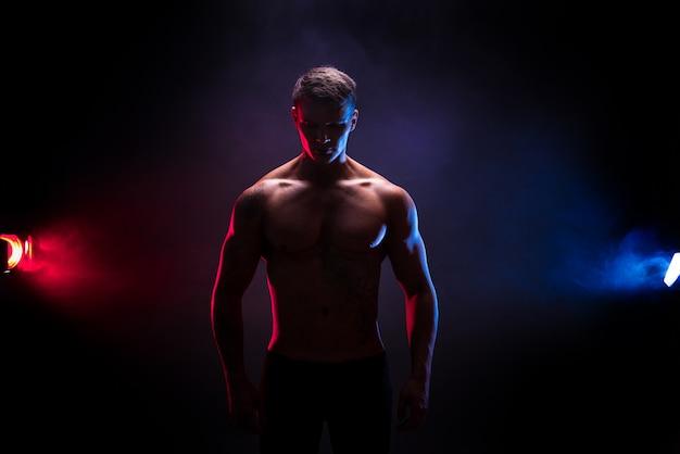 Silhueta incrível fisiculturista. fisiculturista de homem atlético poder bonito. corpo musculoso de aptidão na cena de fumaça de cor escura. macho perfeito. tatuagem, posando. Foto Premium