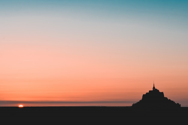 Silhueta negra do mont saint michel em um céu laranja e azul-petróleo Foto Premium