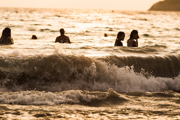 Silhueta pessoas onda mar praia pôr do sol Foto Premium