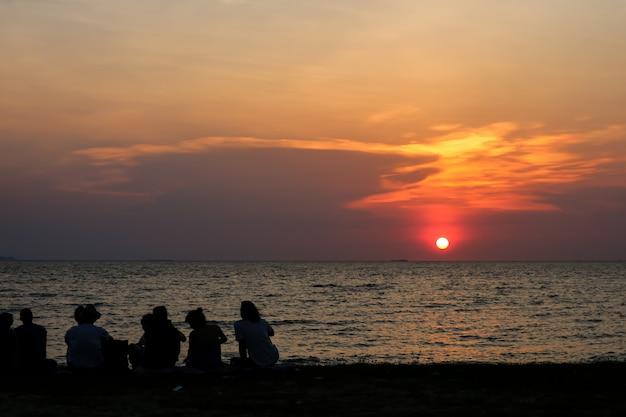 Silhueta pessoas reunião olhar céu pôr do sol na praia Foto Premium