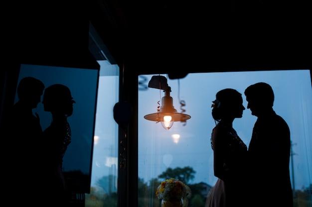 Silhuetas da noiva e do noivo no fundo da janela Foto Premium