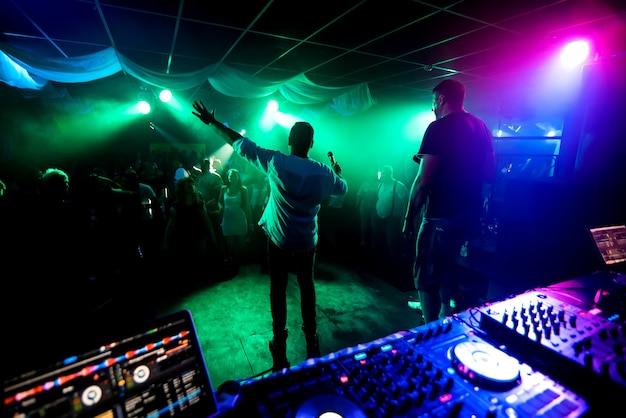 Silhuetas de homens levando músicos na pista de dança no concerto do clube de noite Foto Premium