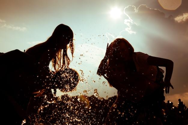 Silhuetas de meninas brincando na água contra o sol Foto Premium
