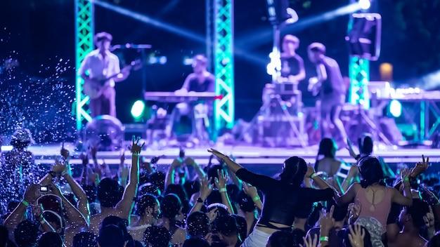 Silhuetas de multidão de concerto na frente de luzes do palco brilhante, festa na piscina Foto Premium