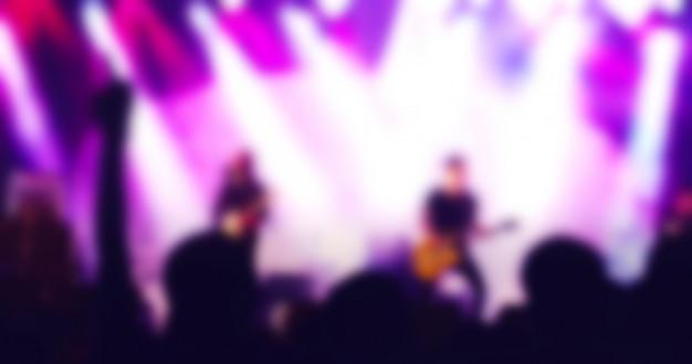 Silhuetas de multidão de concerto na vista traseira do festival multidão levantando suas mãos em luzes brilhantes Foto Premium