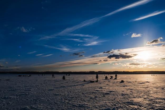 Silhuetas de pescadores que pescam e parafusos de gelo no inverno Foto Premium