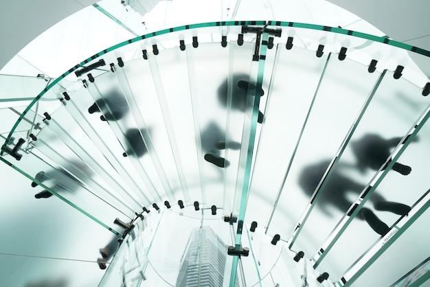 Silhuetas de pessoas andando em uma escada em espiral de vidro Foto Premium