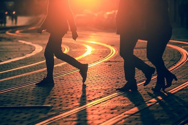 Silhuetas de pessoas andando na rua da cidade e lançando sombras no pavimento com trilhos em bordeaux, textura de grão aplicar Foto Premium