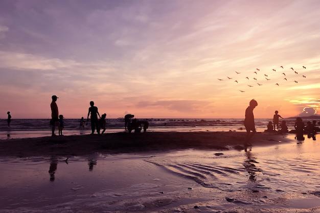 Silhuetas de pessoas na praia tropical no entardecer. Foto Premium