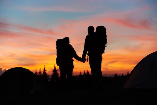Silhuetas de um casal apaixonado, segurando as mãos em pé no topo da montanha enquanto caminhava Foto Premium
