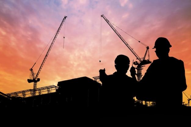 Silueta, de, engenheiros, com, trabalhador, em, construção, predios Foto Premium