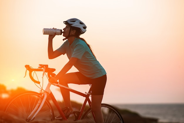 Silueta, de, femininas, ciclista, bicicleta equitação, e, dringking, água, com, mar, o Foto Premium