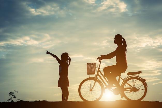 Silueta, de, mãe, com, dela, filha, e, bicicleta Foto gratuita