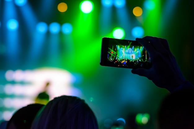 Silueta, de, mãos, com, um, smartphone, em, um, concerto Foto Premium