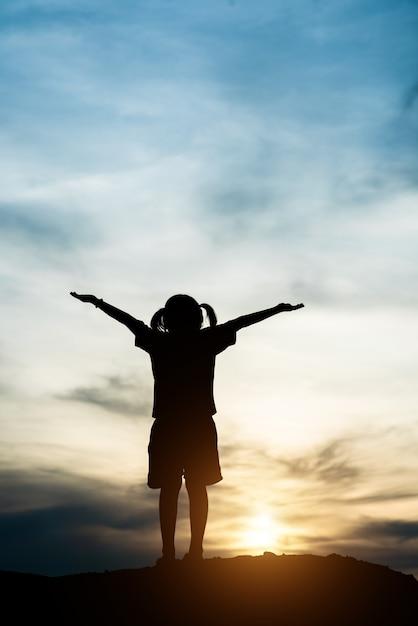 Silueta, de, menininha, levantando mão, para, liberdade, feliz, tempo Foto gratuita