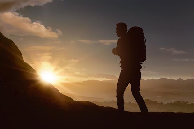 Silueta, de, mochileiro, homem caminhando, a, montanha Foto Premium