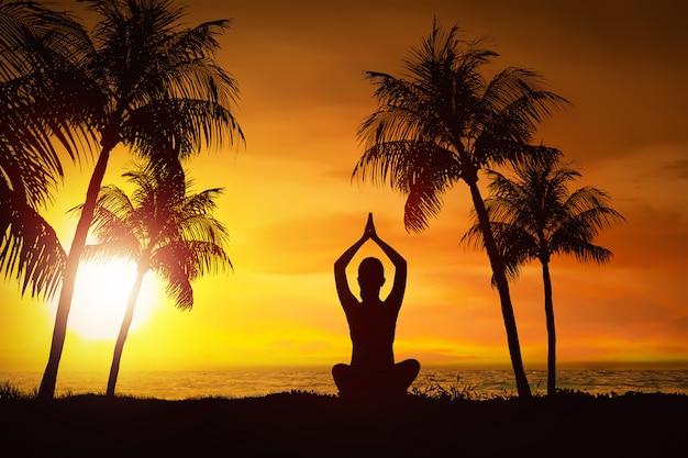 Silueta, de, mulher, fazendo, ioga, com, vista oceano Foto Premium