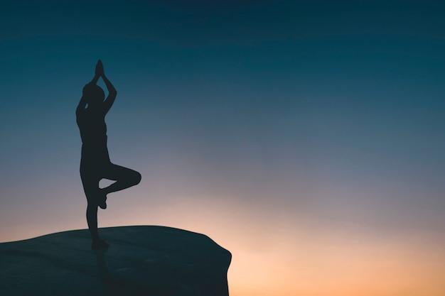 Silueta, de, mulher, fazendo, ioga, ligado, rocha Foto Premium