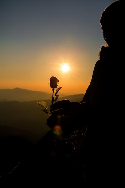 Silueta, de, par, segurando, rosa, ligado, colina, em, a, pôr do sol, tempo, skyline, ligado, fundo Foto gratuita