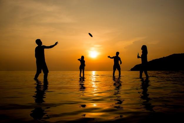 Silueta, de, pessoas jogando, praia, em, pôr do sol Foto Premium