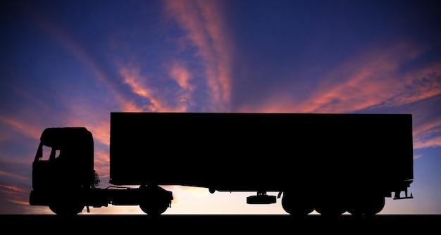 Silueta, de, um, caminhão, ligado, estrada, em, pôr do sol Foto Premium